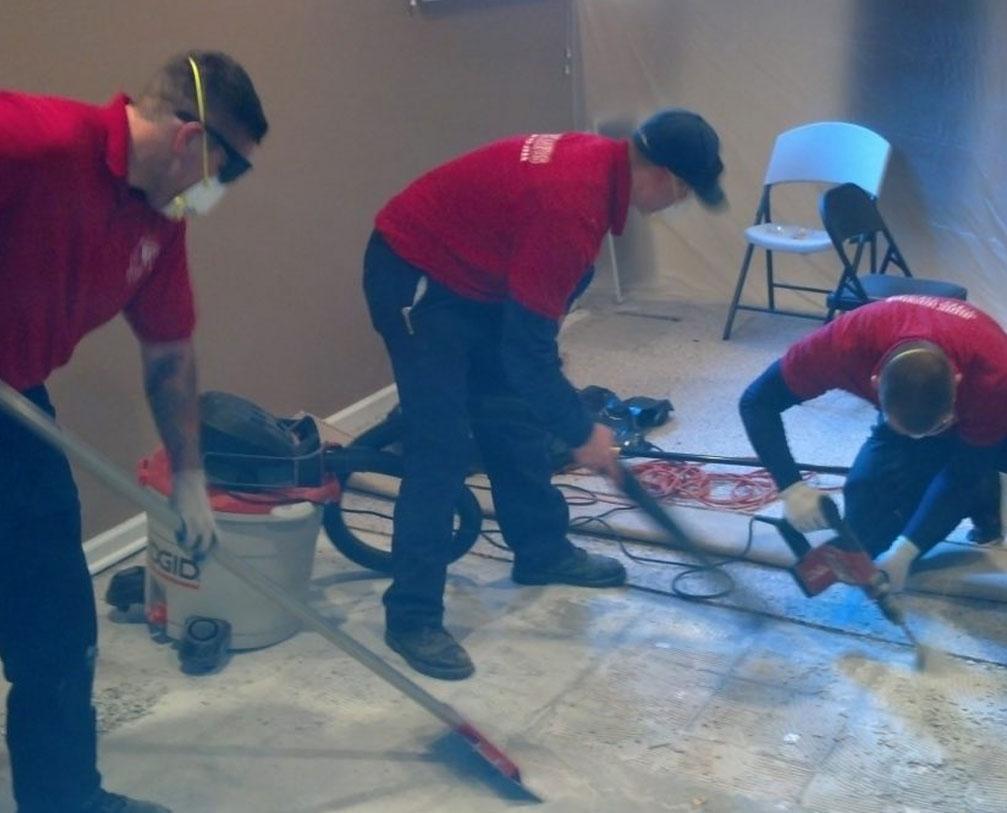 Men in red uniform cleaning floor with machines